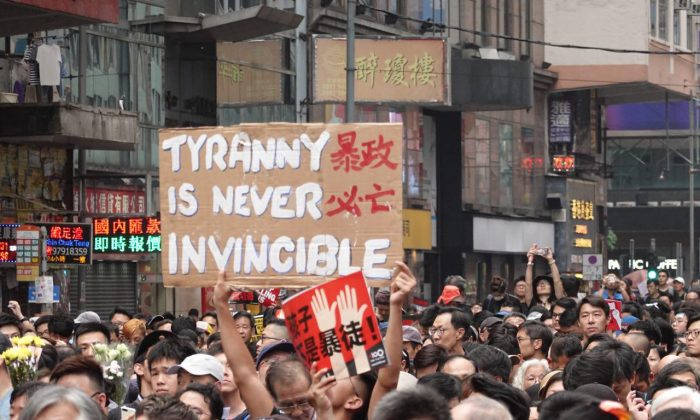 """One protester holds up a sign that reads """"Tyranny Is Never Invincible,"""" in a reference to the Hong Kong government under leader Carrie Lam on June 16, 2019. Another protester holds up a sign in red, with the Chinese characters """"Children Are Not Rioters."""" (Yu Gang/The Epoch Times)"""
