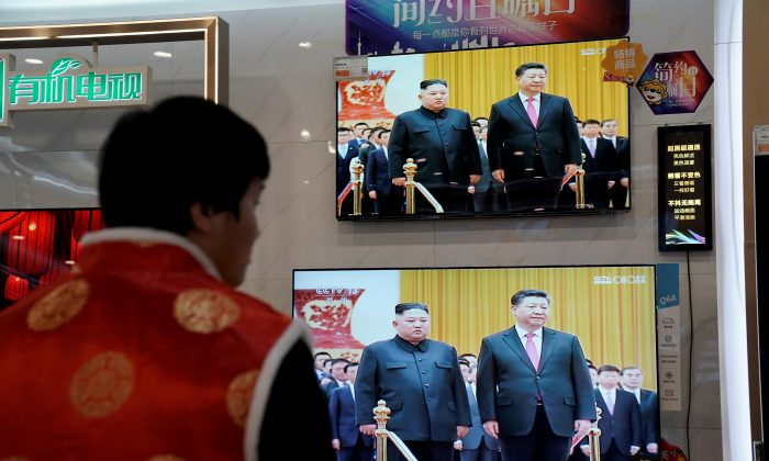 Television screens show Chinese state media CCTV's footage of North Korean leader Kim Jong Un's meeting with Chinese leader Xi Jinping, at an electronics store in Beijing on Jan. 10, 2019. (Jason Lee/Reuters)