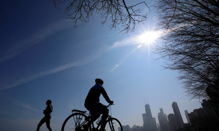 A jogger and a cyclist make their way around Lake Michigan in Chicago, March 21, 2014. (Jim Young/File Photo via Reuters)