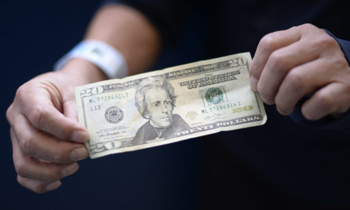 A member of a group of 228 immigrants deported from the United States shows a 20-dollar bill before exchanging it upon arrival at the Air Force base in Guatemala City on Jan. 10, 2018. JOHAN ORDONEZ/AFP/Getty Images