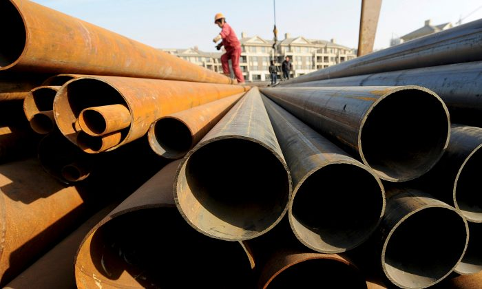 A laborer walks on steel pipes at a steel market in Hefei, Anhui Province, China on Dec. 31, 2009.  (Reuters)