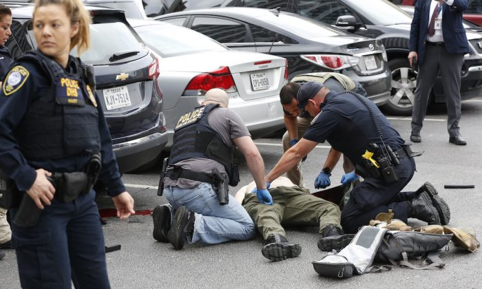 Law enforcement hovers over the shooter in a parking lot after he fired shots at the Earle Cabell federal courthouse in downtown Dallas on June 17, 2019. (Tom Fox/The Dallas Morning News)