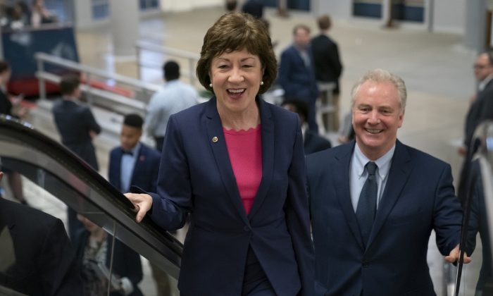 Republican Sen. Susan Collins of Maine, joined by Sen. Tim Kaine (D-Va.) right, arrives at the Capitol to extend her perfect Senate voting record to 7,000, as she prepares for a 2020 campaign, in Washington on June 18, 2019. (J. Scott Applewhite/AP Photo)