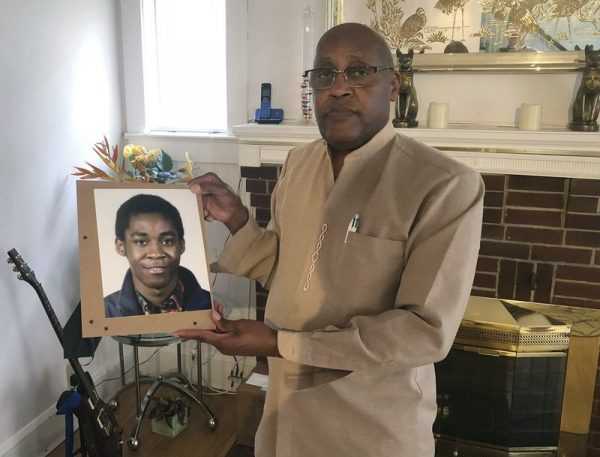Father of deceased worker holds photo