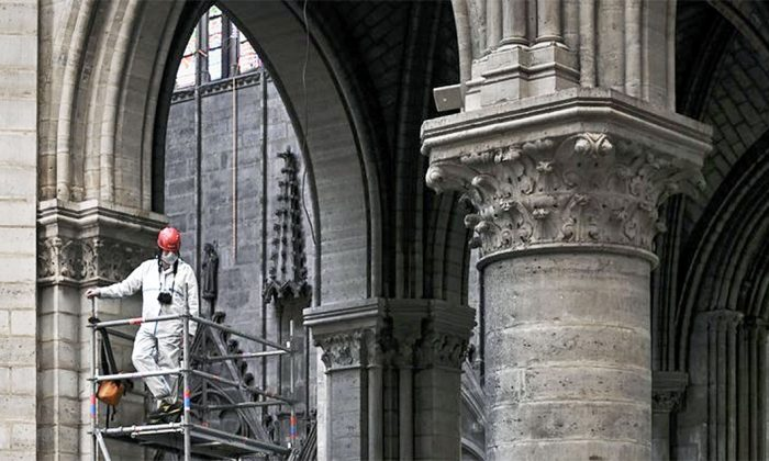 A worker stands on scaffolding during preliminary work inside the Notre Dame de Paris Cathedral in Paris on May 15, 2019. (Philippe Lopez/Pool via AP, File)