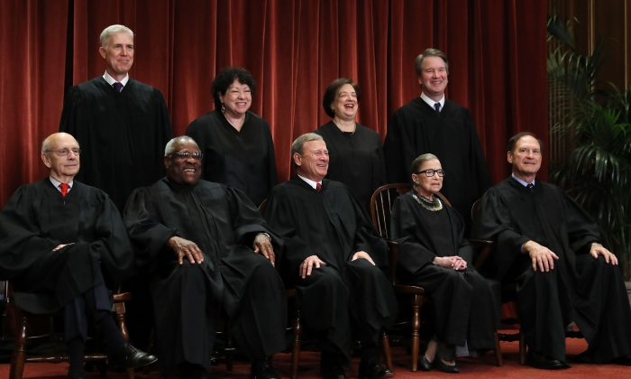 United States Supreme Court (Front L-R) Stephen Breyer, Clarence Thomas, Chief Justice John Roberts, Ruth Bader Ginsburg, Samuel Alito, Jr., (Back L-R) Neil Gorsuch, Sonia Sotomayor, Elena Kagan and Brett Kavanaugh in the Supreme Court building in Washington on Nov. 30, 2018. (Chip Somodevilla/Getty Images)