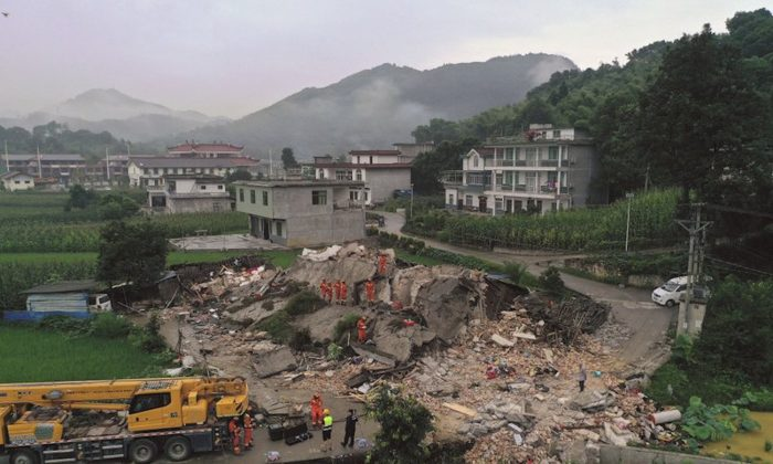 Rescue workers search for trapped people at a collapsed building after an earthquake in Shuanghe Town in Changning County of Yibin City, southwest China's Sichuan Province on June 18, 2019, a day after a strong earthquake hit the area. (Zeng Lang/Xinhua via AP)