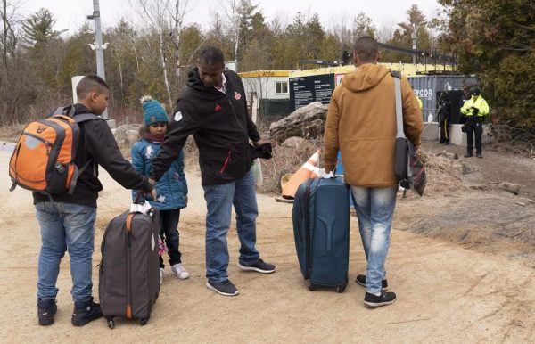 A family, claiming to be from Colombia, gets set to cross the border into Canada from the United States as asylum seekers on April 18, 2018 near Champlain, NY. (Paul Chiasson/The Canadian Press)