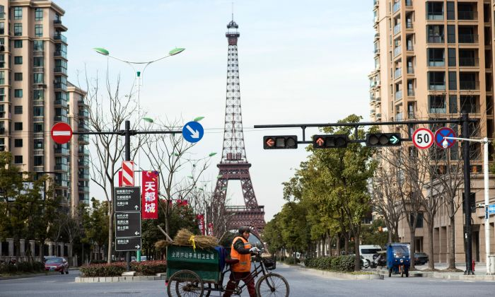 "A street cleaner passes by a replica of Eiffel Tower in Tianducheng, or ""Sky Capital City,"" a luxury real estate development in Hangzhou in eastern China's Zhejiang province on January 26, 2016. (Johannes Eisele/AFP/Getty Images)"