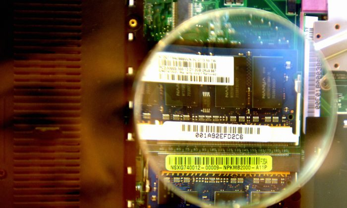 A woman looks through a magnifier to see a 2GB RAM from a notebook during the semi-tech show in Taipei 10 in May 2007.  (Sam Yeh/AFP/Getty Images)