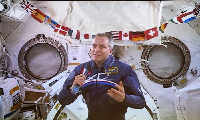 Canadian Space Agency astronaut David Saint-Jacques responds to a question during his last press conference in orbit before returning to Earth on June 24, seen on a giant screen in Saint-Hubert, QB. on June 19, 2019. (Paul Chiasson/The Canadian Press)