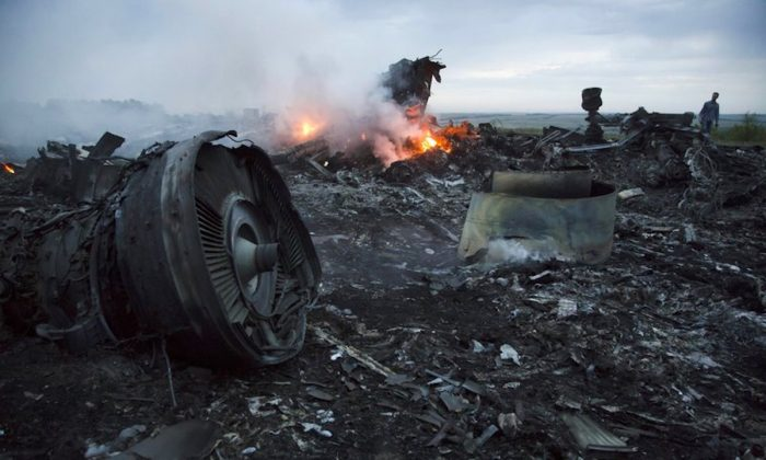 A man walks amongst the debris at the crash site of a passenger plane near the village of Hrabove, Ukraine, on July 17, 2014. (Dmitry Lovetsky/AP Photo)