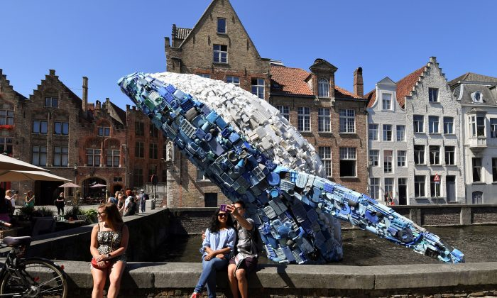 Tourists pose for a selfie picture with a 12-metre installation depicting a whale, made up of five tons of plastic waste pulled out of the Pacific Ocean, displayed in Brugges, on July 14, 2018 for the 2018 Bruges Triennial. (John Thys/AFP/Getty Images)