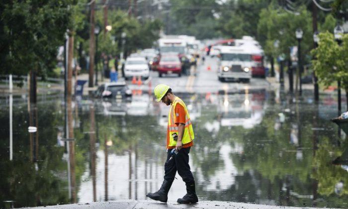 A utility worker walks the edge of the floodwaters submerging Broadway in Westville, N.J., on June 20, 2019. (Matt Rourke/Photo via AP)