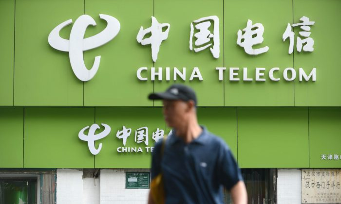 A man walks past a China Telecom store in Wuhan, in central China's Hubei province on Aug. 21, 2013. (STR/AFP/Getty Images)