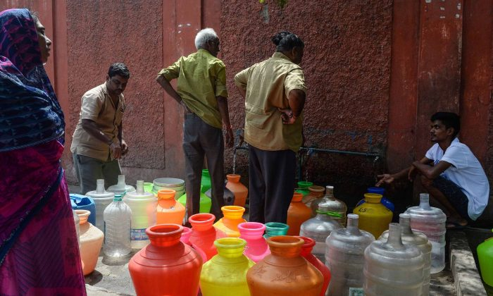 Indian residents stand around with plastic pots filled with drinking water at a distribution point in Chennai on June 19, 2019. (Arun Sankar/AFP/Getty Images)
