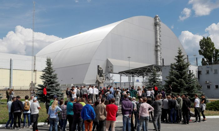 Visitors stand outside the New Safe Confinement (NSC) structure over the old sarcophagus covering the damaged fourth reactor at the Chernobyl Nuclear Power Plant, in Chernobyl, Ukraine June 2, 2019. (Valentyn Ogirenko/Reuters)