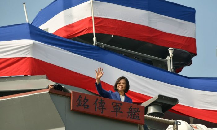 Taiwan's President Tsai Ing-Wen waves to assembled guests from the deck of the 'Ming Chuan' frigate during a ceremony to commission two Perry-class guided missile frigates from the United States into the Taiwan Navy, in the southern port of Kaohsiung on Nov. 8, 2018. (Chris Stowers/AFP/Getty Images)