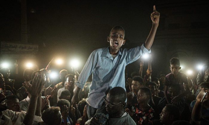 People chant slogans as a young man recites a poem, illuminated by mobile phones, before the opposition's direct dialog with people in Khartoum, Sudan on June 19, 2019.(YASUYOSHI CHIBA/AFP/Getty Images)