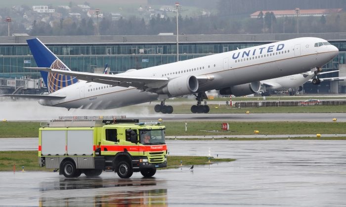 A vehicle of the airport rescue and firefighting services stands in front as a Boeing 767-400ER aircraft of United Airlines takes off from Zurich airport on April 9, 2019. (Arnd Wiegmann/Reuters)
