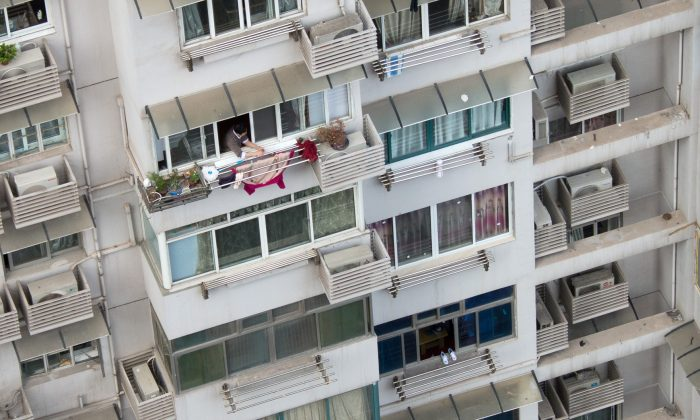 A man hanging clothes off his balcony. (Johannes Eisele/AFP/Getty Images)