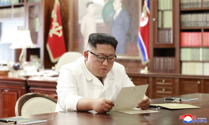North Korean leader Kim Jong Un reads a letter from President Donald Trump in a photo released by North Korean state media on June 23. (KCNA)