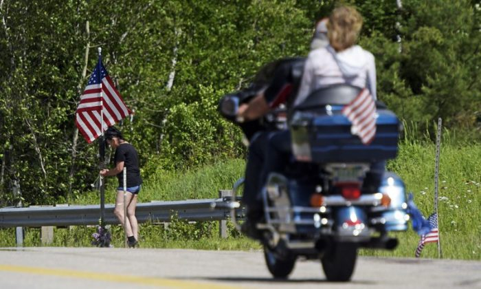 A motorcycle passes as a woman leaves flowers at the scene of a fatal accident on Route 2 in Randolph, N.H., on June 22, 2019. (Paul Hayes/Caledonian-Record via AP)