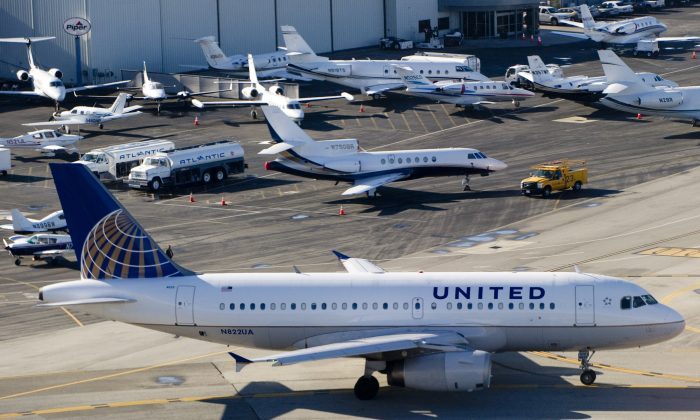 A United Airlines Airbus A319 airplane waits to take off alongside private jets at John Wayne Airport in Santa Ana, Calif., on Feb. 16, 2012. (Saul Loeb/AFP/Getty Images)