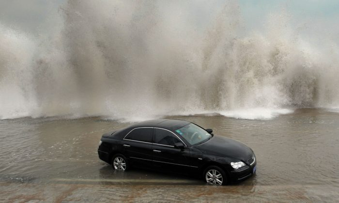 A car surrounded by water and waves. (STR/AFP/GettyImages)