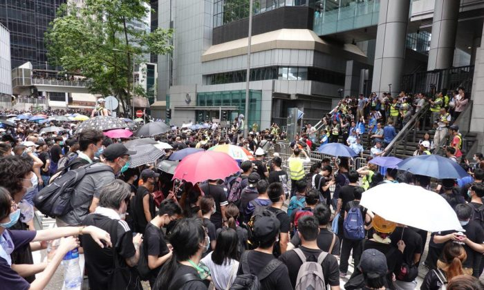 Protesters surround the Hong Kong police headquarters on June 21, 2019, in protest against controversial extradition legislation that would facilitate the erosion of the cities freedoms by mainland China. (Yu Gang/The Epoch Times)
