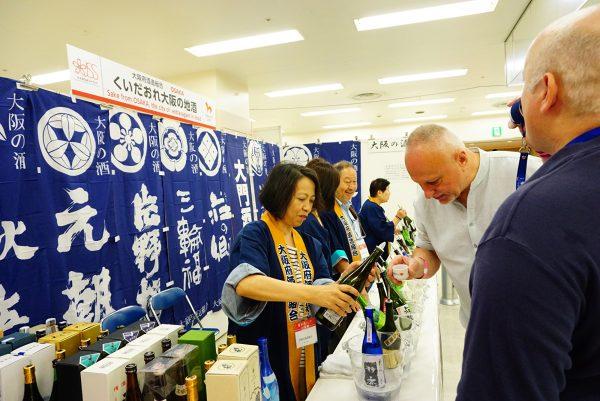 international visitors taste sake at the japanese sake fair in tokyo