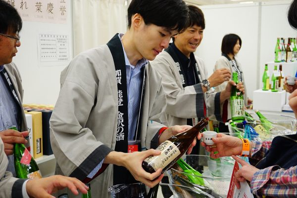 man enjoys a sample of sake at the japanese sake fair in tokyo