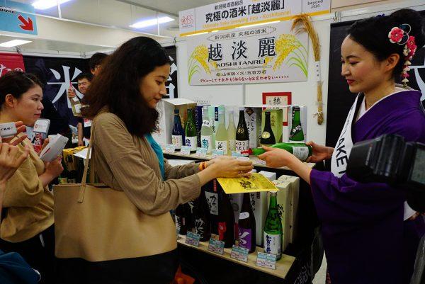 woman enjoys a tasting of sake at japanese sake fair