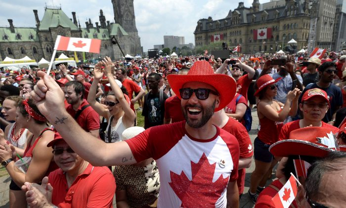 People cheer during Canada Day celebrations on Parliament Hill in Ottawa on July 1, 2018. (THE CANADIAN PRESS/Justin Tang)