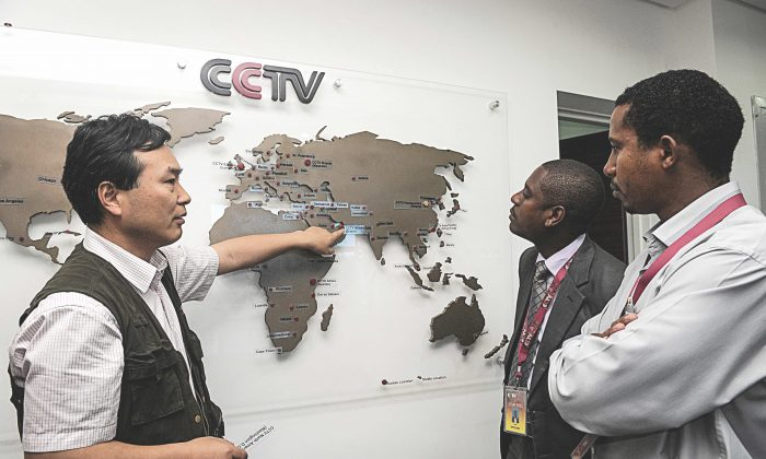 Pang Xinhua (L), managing editor of China Central Television  Africa, talks to local journalists in Nairobi, Kenya, as he shows them how the organization has expanded in different parts of Africa, on June 12, 2012.  (SIMON MAINA/AFP/GettyImages)