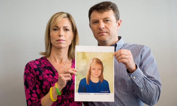 Parents of missing girl Madeleine McCann, Kate (L) and Gerry McCann (R) pose with an artist's impression of how their daughter might look now at the age of nine ahead of a press conference in central London on May 2, 2012. (LEON NEAL/AFP/GettyImages)