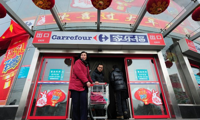 Shoppers step out of a Carrefour store in Beijing on January 27, 2011. The French retailer announced on June 23 it will sell the majority of its China business to local e-commerce firm Suning.com. (Frederic J. Brown/AFP/Getty Images)
