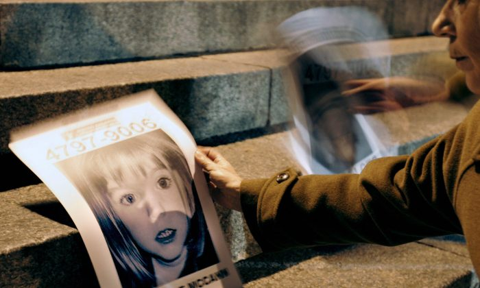 A Woman holding a picture of Madeleine McCann.