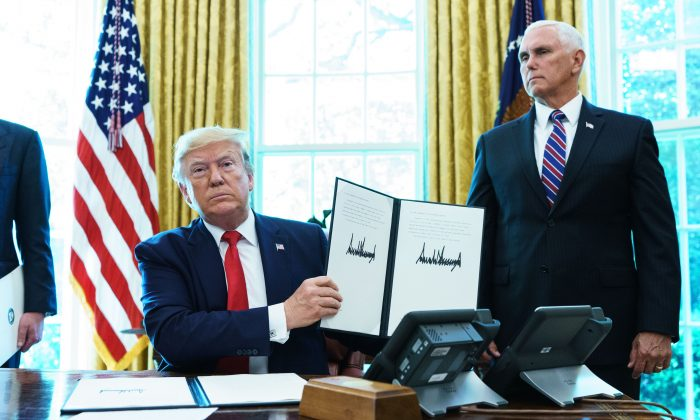 US President Donald Trump shows an executive order on sanctions on Iran's supreme leader in the Oval Office of the White House on June 24, 2019. (Photo by MANDEL NGAN / AFP)        (Photo credit should read MANDEL NGAN/AFP/Getty Images)
