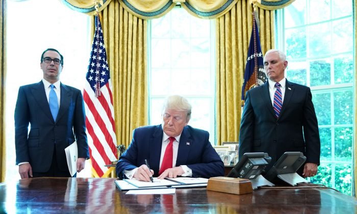 President Donald Trump signs with Vice President Mike Pence(R) and Secretary of Treasury Steven Mnuchin at the White House on June 24, 2019, 'hard-hitting sanctions' on Iran. (Mandel Ngan/AFP/Getty Images)