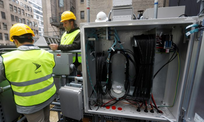 Sprint technicians work on the installation of 5G technology next to fiber cables on top of a building in New York City, U.S. on June 11, 2019. (Shannon Stapleton/Reuters)