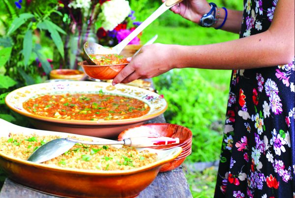 young girl ladles Gazpacho into bowl