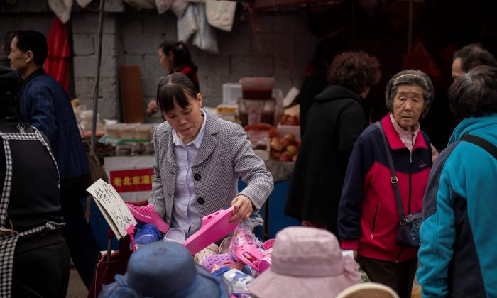 A woman looks at shoes at a market in Beijing on April 23, 2019. (Nicolas Asfouri/AFP/Getty Images)