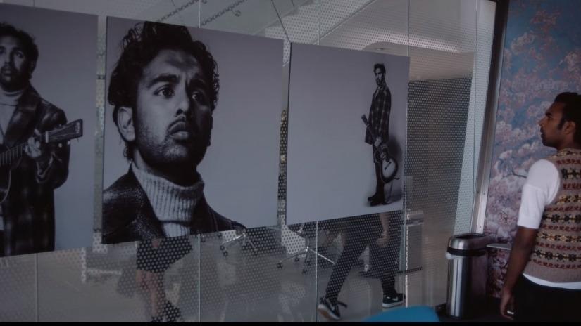 man looking at big photo of himself