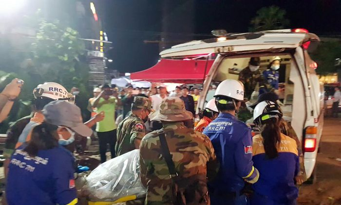 Rescuers enter a victim onto an ambulance at a site of a collapse in Preah Sihanouk Province, Cambodia on June 23, 2019. Rescuers on June 24 were continuing to search the rubble of a building that collapsed while under construction in a Cambodia beach town, killing dozens of workers as they slept in the unfinished condominium that was doubling as their housing. (Preah Sihanouk provincial authorities via AP)
