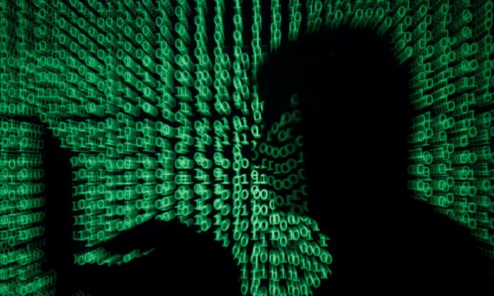 A man holds a laptop computer as cyber code is projected on him in this illustration picture taken on May 13, 2017. (Kacper Pempel/Reuters)