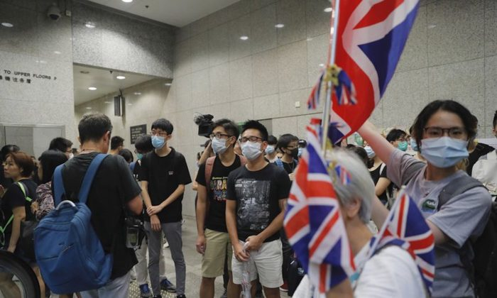 Protesters carry British flags as they block the lobby of the Hong Kong Revenue Tower in Hong Kong on June 24, 2019. Hong Kong has been rocked by major protests for the past two weeks over legislative proposals that many view as eroding the territory's judicial independence and, more broadly, as a sign of the Chinese regime's efforts to chip away at the city's freedoms. (Kin Cheung/AP)