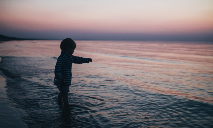 A Child playing at the seashore.