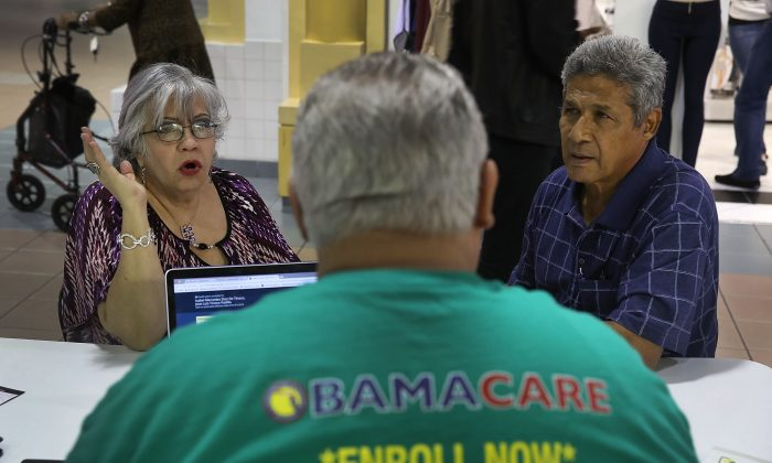 Isabel Diaz Tinoco  (L) and Jose Luis Tinoco speak with Otto Hernandez, an insurance agent from Sunshine Life and Health Advisors, (Joe Raedle/Getty Images)