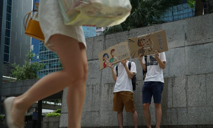 Protestors hold up signs to apologize for a demonstration that jammed the entrance of a government tax office in Hong Kong on June 25, 2019. Hong Kong protestors handed out flyers, held up signs, and bowed to passersby Tuesday to apologize for a sit-in demonstration the day before that blocked access to a government office for nearly two hours. (Dake Kang/AP)